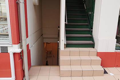 建物の横側から地下へ進み、ドアを開けてお入りください。